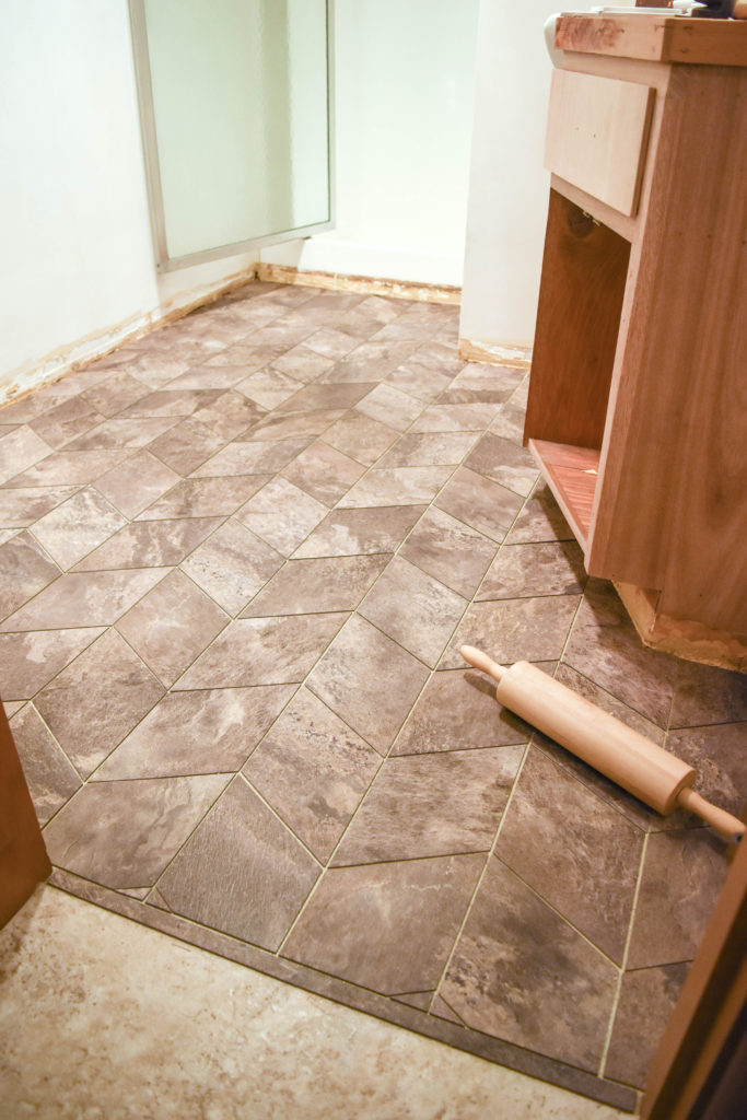How to lay custom vinyl tile floors - great option for a bathroom renovation and easy way to cover up existing floors! Cut vinyl tiles to shapes and lay them in a pattern.