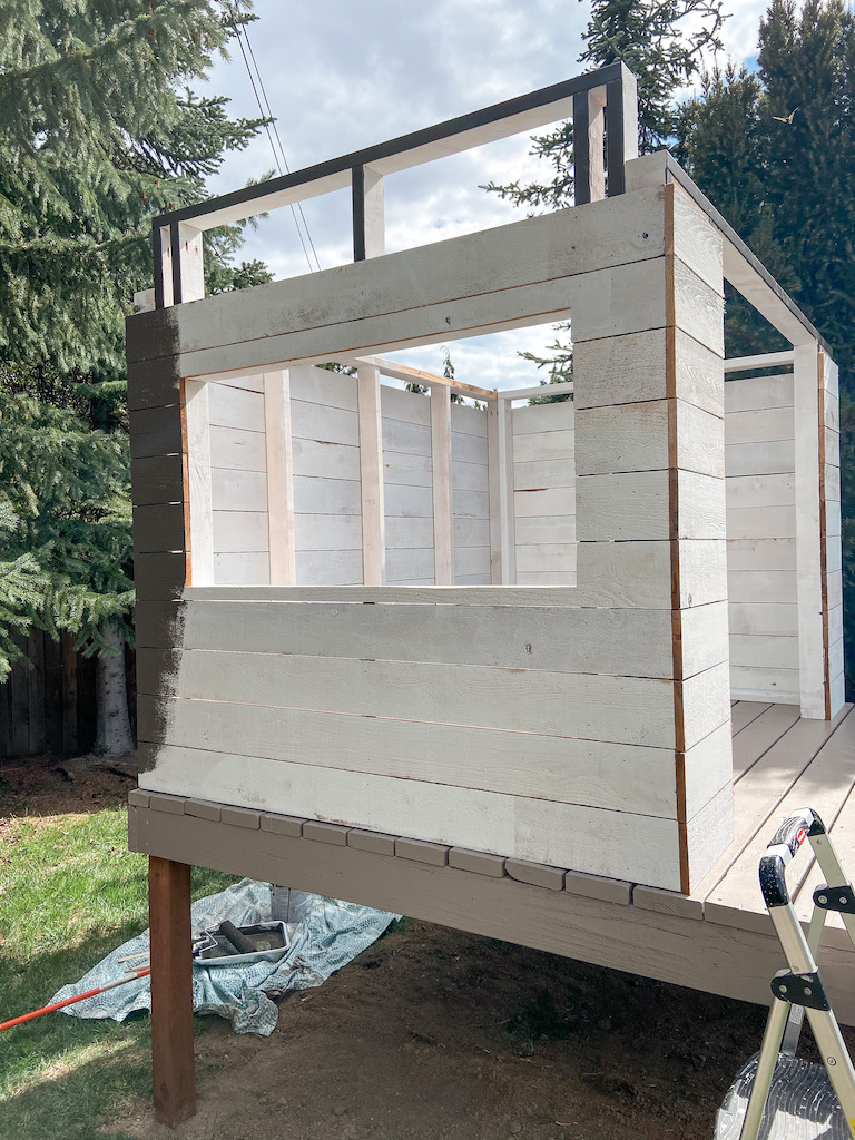 DIY modern playhouse siding with cedar fence boards. Primed with oil-based paint and painted Black Fox (SW)   EffieRow.com  #diyplayhouse #diycubbyhouse #cubbyhouse #playhouse #modernplayhouse #mcmplayhouse #playhousesiding #cubbyhousesiding #sherwinwilliamsblackfox